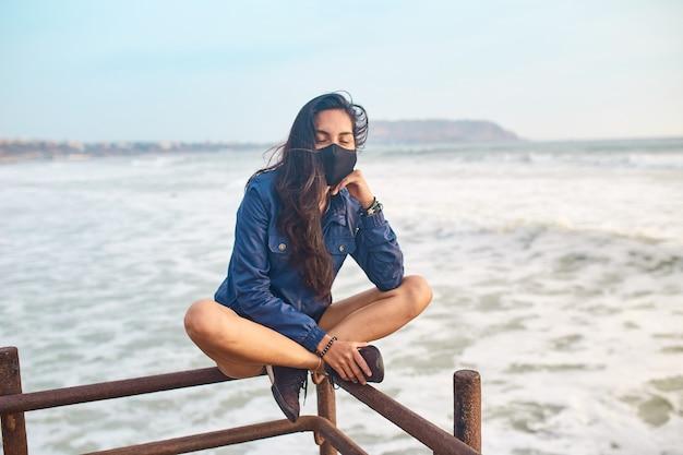 桟橋にフェイスマスクを身に着けている若い女性。日没時のアウトドアスポーツ。日没で休んでいる無料の女性
