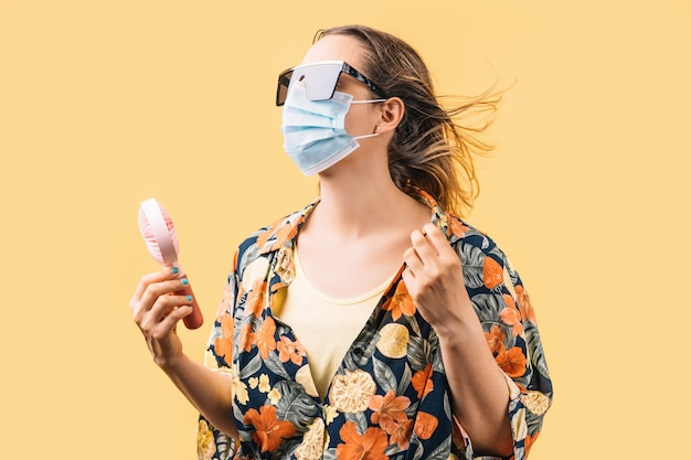Young woman wearing face mask, sunglasses and flowered shirt holding small fan on yellow background