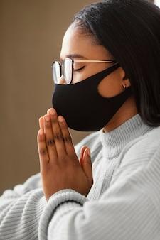 Giovane donna che indossa una maschera per il viso mentre prega