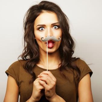 Молодая женщина в накладных усах. готов к вечеринке.