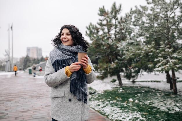 フレイファッションコートと青いスカーフを身に着けている若い女性は、冬の雪に覆われた公園に行くためにコーヒーと一緒に立っています。
