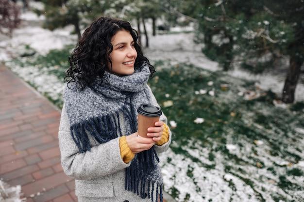 Молодая женщина в пальто моды frey и синем шарфе стоит с кофе, чтобы пойти в зимний снежный парк.
