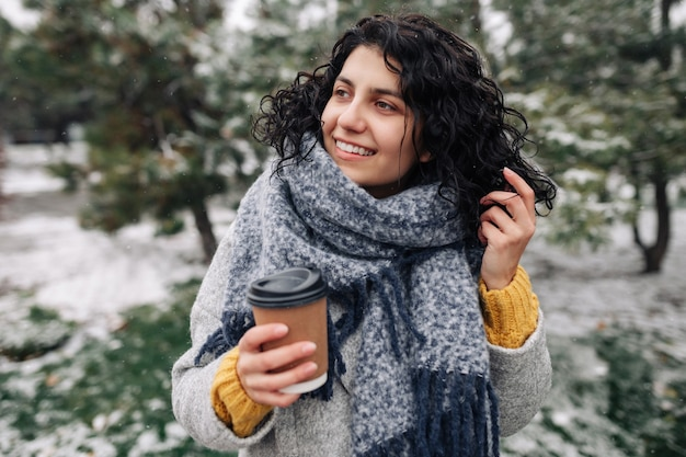 Young woman wearing frey fashion coat and blue scarf stands with a coffee to go at a winter snowy park.