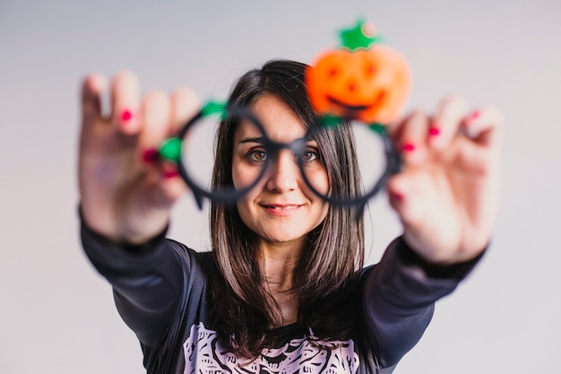 Young woman wearing funny halloween glasses and smiling. lifestyle indoors. skeleton costume