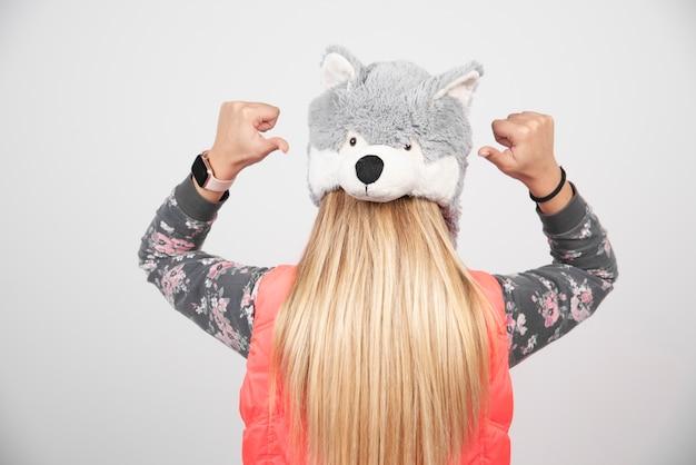 흰 벽에 재미있는 모자를 쓰고 젊은 여자.