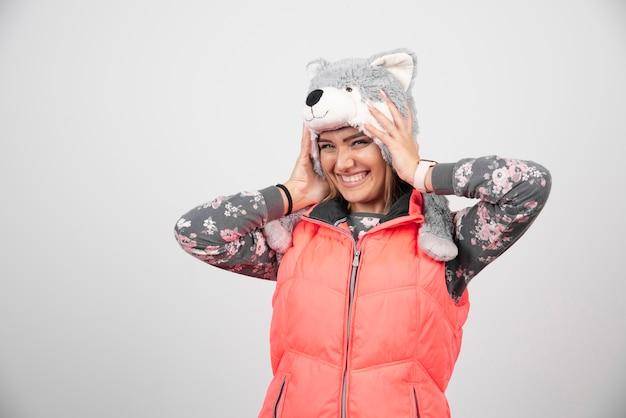 Giovane donna che indossa un cappello divertente su un muro bianco.
