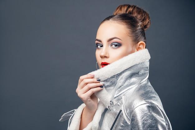 Young woman wearing futuristic silver fashion jacket.