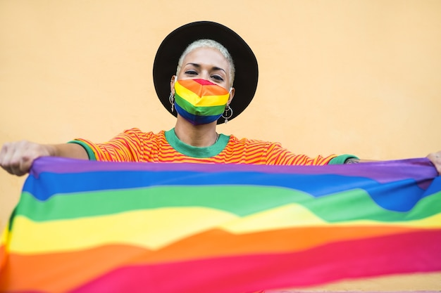 Young woman wearing gay pride mask - lgbt rights concept
