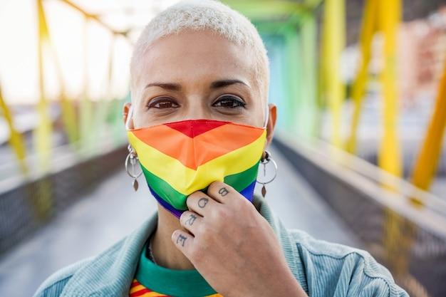 ゲイプライドマスクを身に着けている若い女性-lgbtの権利、多様性、寛容、性同一性の概念