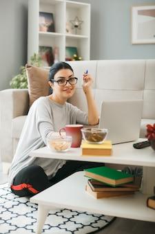 Giovane donna con gli occhiali usato laptop seduto sul pavimento dietro il tavolino in soggiorno