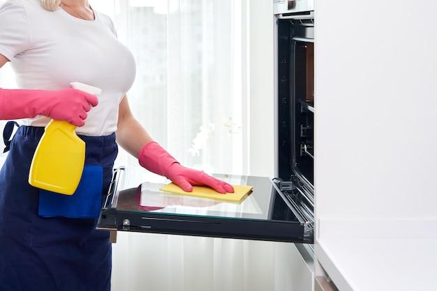 Молодая женщина в перчатках чистки духовки на кухне. концепция клининговых услуг