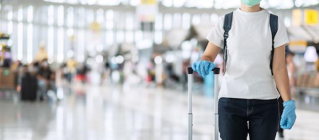 荷物のハンドルを保持している手袋を着用して若い女性
