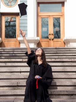 Young woman wearing graduation gown in front of university