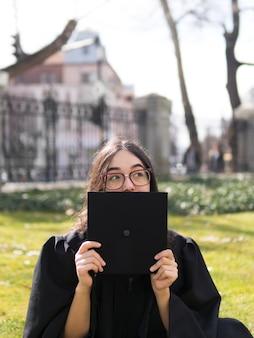 外の卒業式のガウンを着た若い女性