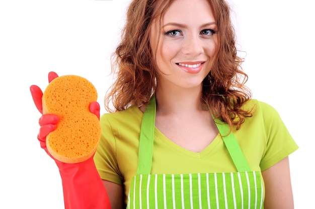 Young woman wearing green apron and rubber gloves with sponge, on white