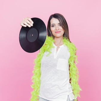 Young woman wearing green boa showing vinyl record in hand standing against pink backdrop