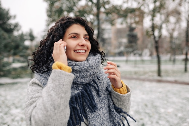 Young woman wearing grey coat and blue scarf talking on the mobile phone at a snowy winter park.