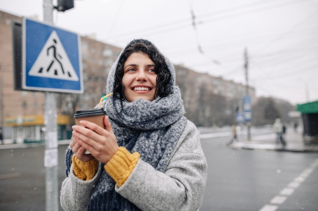 Young woman wearing a grey fashion coat and a blue scarf stands on a crosswalk with a coffee paper cup in her hands.