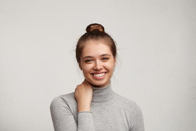 Молодая женщина в серой водолазке