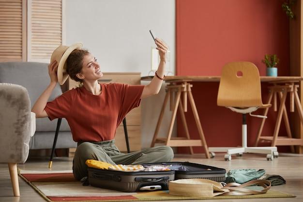 Молодая женщина в шляпе и делает селфи на своем мобильном телефоне, сидя на полу в комнате
