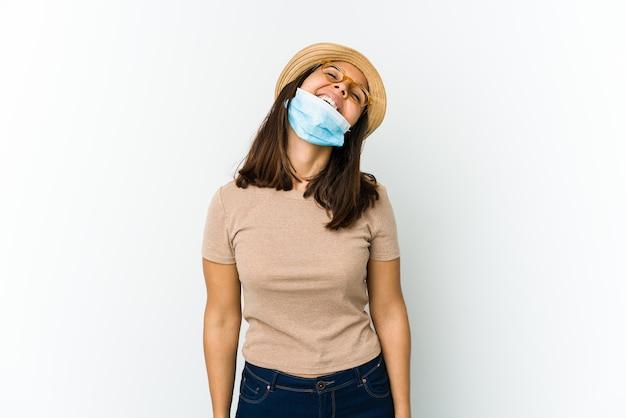 Молодая женщина в шляпе и маске для защиты от covid изолирована на белой стене расслабленно и счастливо смеется, вытянув шею, показывая зубы