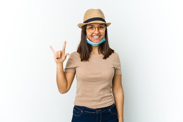 Молодая женщина в шляпе и маске для защиты от covid изолирована на белой стене, показывая жест рогов как революционную концепцию