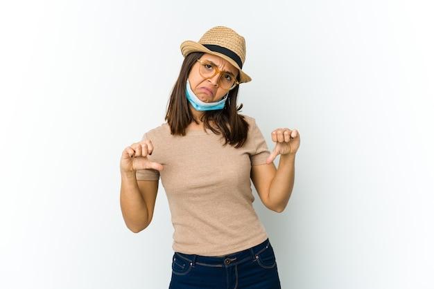 흰색 벽에 고립 된 covid로부터 보호하기 위해 모자와 마스크를 착용하는 젊은 여자는 아래로 엄지 손가락을 보이고 싫어하는 표현