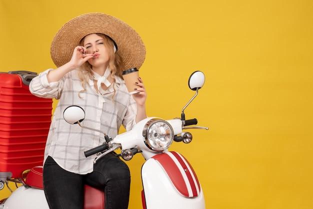 젊은 여자 모자를 쓰고 오토바이에 앉아 완벽한 제스처를 만드는 커피를 들고
