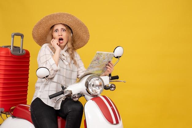 젊은 여성이 모자를 쓰고 오토바이에 앉아 노란색에 놀란 느낌을 들고지도를 들고