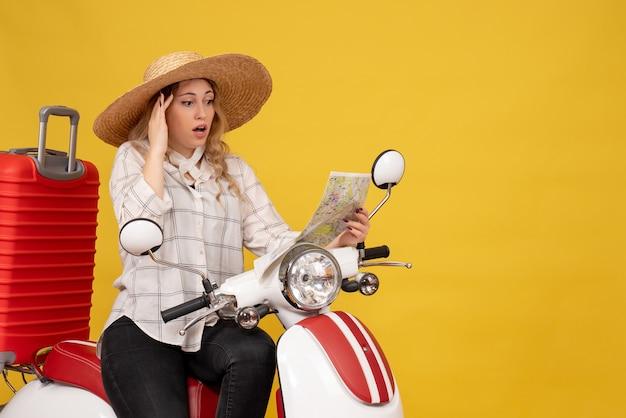 젊은 여자 모자를 쓰고 오토바이에 앉아 노란색에 혼란스러운 얼굴 표정으로지도를보고