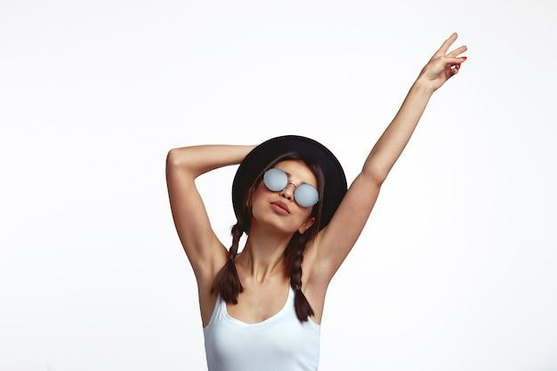 흰 벽에 평화 제스처를 보여주는 모자와 선글라스를 착용하는 젊은 여자