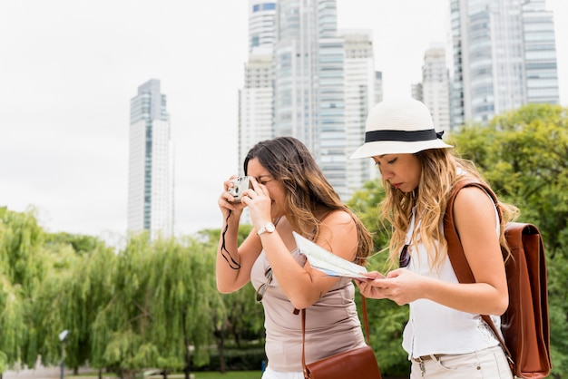 Young woman wearing hat reading the map and her female friend taking photograph from camera