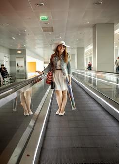 空港ターミナルのエスカレーターに立つ帽子をかぶった若い女性