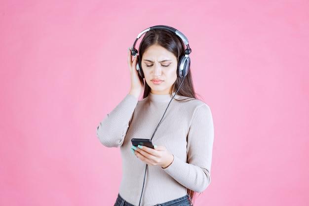 젊은 여성이 헤드폰을 착용하고 그녀의 재생 목록에서 음악을 즐기지 않습니다.