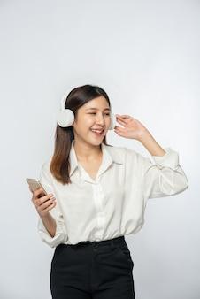 Молодая женщина в наушниках и слушает музыку на смартфоне