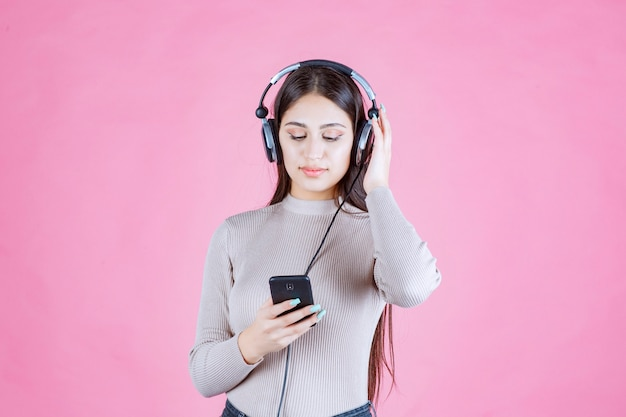 Молодая женщина в наушниках и установка музыки на свой смартфон