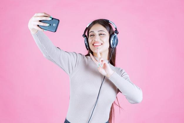 헤드폰을 착용 하 고 그녀의 selfie를 복용하는 젊은 여자