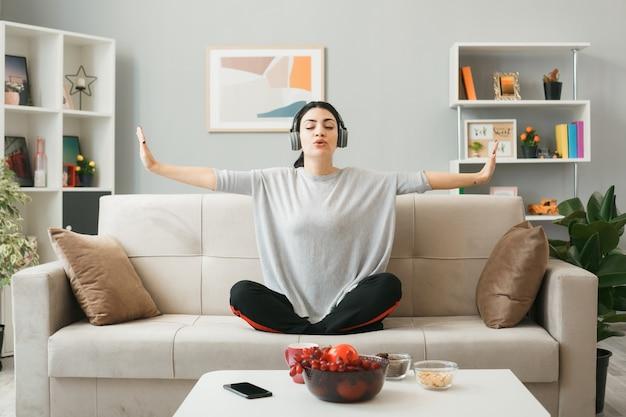 Молодая женщина в наушниках занимается йогой, сидя на диване за журнальным столиком в гостиной