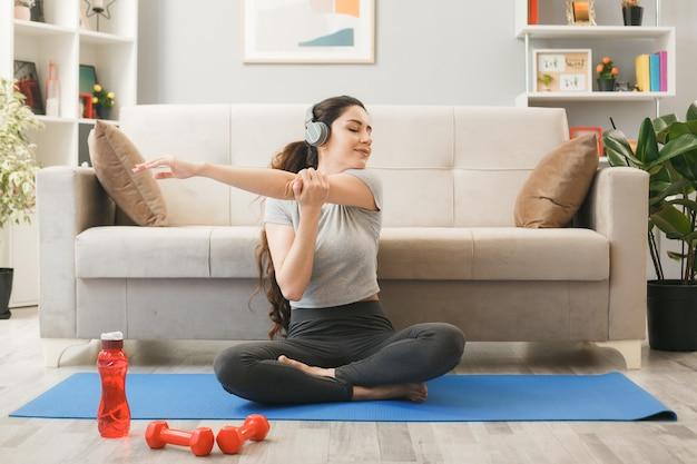 リビングルームのソファの前でヨガマットで運動するヘッドフォンを身に着けている若い女性