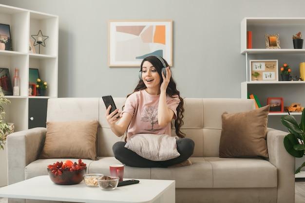 Молодая женщина в наушниках держит и смотрит на телефон, сидя на диване за журнальным столиком в гостиной