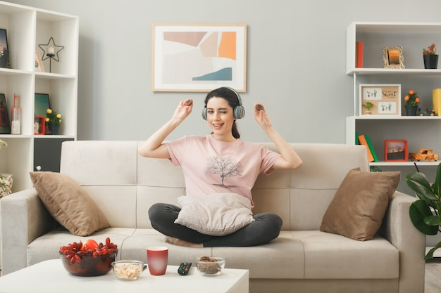 Молодая женщина в наушниках держит печенье, занимается йогой, сидя на диване за журнальным столиком в гостиной
