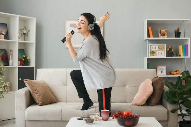 Young woman wearing headphones holding tv remote sings standing on sofa behind coffee table in living room