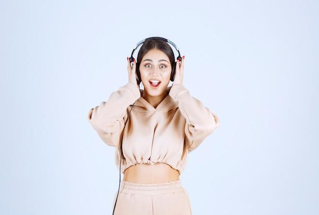 Giovane donna che indossa le cuffie e ascolta la sua playlist con divertimento