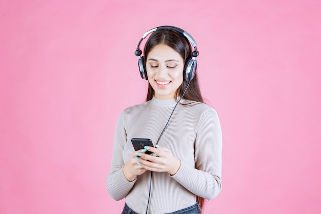 Young woman wearing headphones and setting music at her smartphone