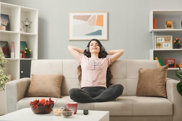 Молодая женщина в наушниках, сидя на диване за журнальным столиком в гостиной