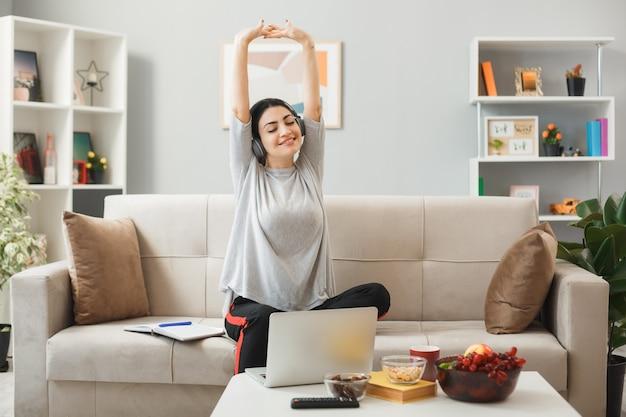 거실에서 커피 테이블 뒤에 소파에 앉아 헤드폰을 착용하는 젊은 여자