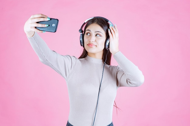 Young woman wearing headphones and taking her selfie