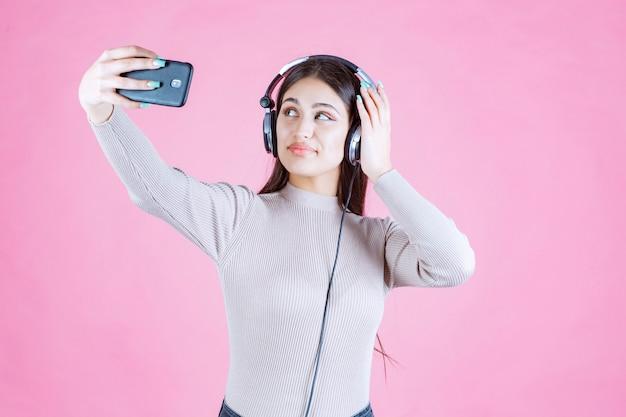 Giovane donna che indossa le cuffie e prendendo il suo selfie