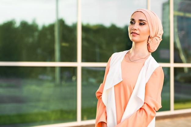 街でヒジャーブのヘッドスカーフを身に着けている若い女性。