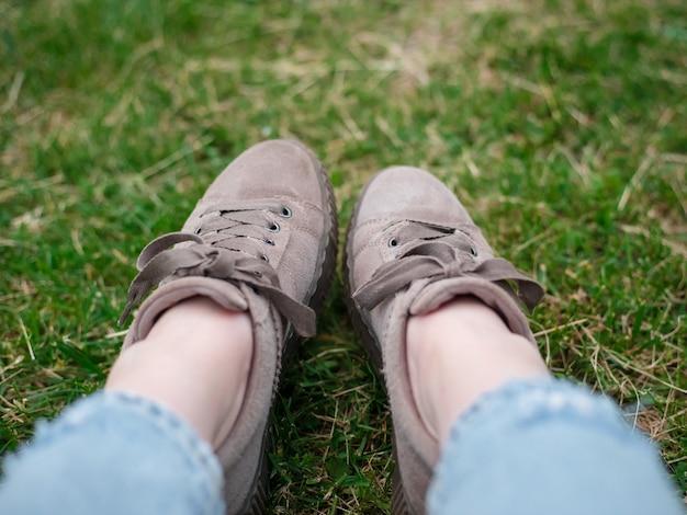 푸른 잔디에 앉아 청바지와 운동화를 입고 젊은 여자, 가까이